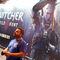 'Witcher Wild Hunt': Un visitante de la feria con el cartel de fondo del juego Witcher Wild Hunt.