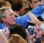 George W. Bush saluda a un grupo de seguidores durante un mitin.