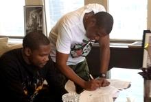 Jay-Z firma el contrato ante Kevin Durant.   Foto: Twitter
