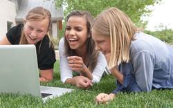 Adolescentes contemplando un vídeo por internet. | Corbis