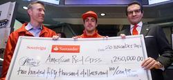 Fernando Alonso entrega un cheque a Cruz Roja. | Santander.com