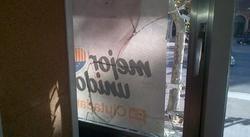 Una de las ventanas de la sede central de Ciudadanos, completamente destrozada por las pedradas.