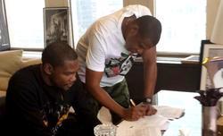 Jay-Z firma el contrato ante Kevin Durant. | Foto: Twitter