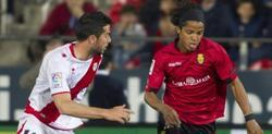 Giovani dos Santos (d) se lleva el balón ante Jordi Amat. | EFE