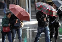 Varias personas con paraguas en San Sebastián | EFE