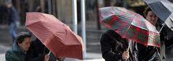 Un grupo de personas se protegen de la lluvia y el viento.