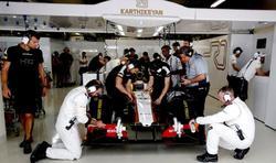 Mecánicos del equipo HRT trabajan en el coche de Karthikeyan en el pasado GP de Brasil.   Cordon Press