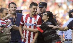 David Villa es abrazado por una aficionada al salir custodiado del Vicente Calderón tras su presentación.   EFE