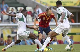 Iniesta controla la pelota ante Echiejile (i) y Obi Mikel. | EFE