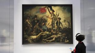 Mujer contemplando 'La libertad guiando al pueblo' en el museo Louvre de Lens. | Cordon Press