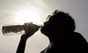 Un hombre bebe agua para hidratarse ante el calor | Archivo
