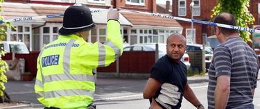 Un policía habla con los vecinos junto al lugar del crimen | EFE