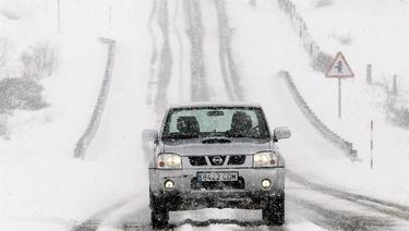 Un coche circula por una carretera nevada en Cantabria | EFE