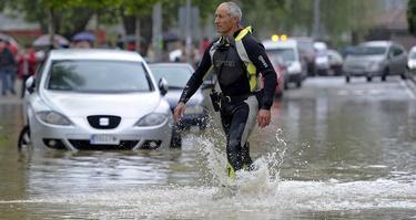 Un bombero atraviesa una de las calles inundadas en el barrio de la Rochapea de Pamplona | EFE