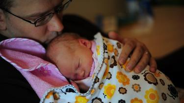 Un padre cuida de su bebé | Wikipedia