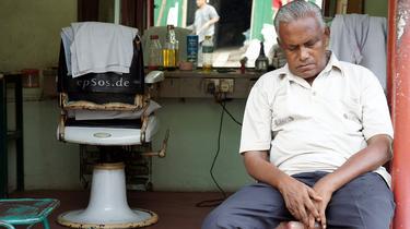 Un hombre duerme frente a una peluquería | Archivo