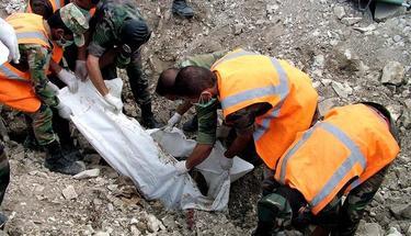 Miembros de la defensa civil de Siria removiendo un cuerpo de una tumba común. | Efe