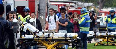 Jóvenes pasan junto a los vehículos medicalizados durante la evacuación en Santa Mónica | EFE