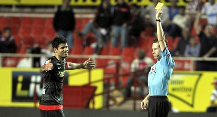 El árbitro González González muestra la amarilla a Diego Costa durante el Sevilla-Atlético de Madrid. | Cordon Press