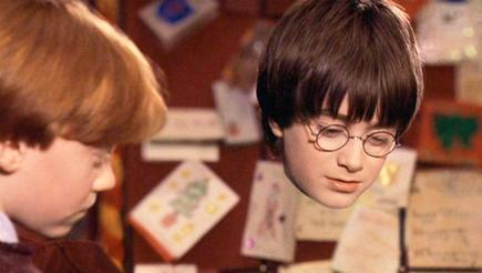Harry Potter vistiendo (de cuello para abajo) la capa de invisibilidad en la primera película de la saga